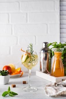 Bebida fresca de mojito con romero, limón y naranja sobre fondo blanco de madera, espacio de copia