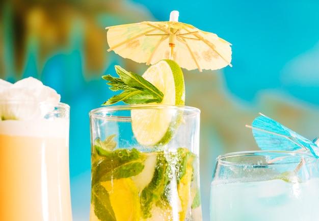 Bebida fresca con rodajas de limón y menta en vidrio decorado con sombrilla.