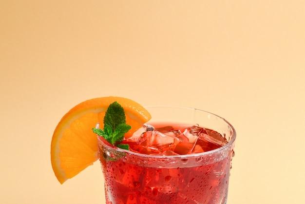 Bebida fresca roja con hielo, pomelo y menta sobre un fondo beige. espacio para texto o diseño.