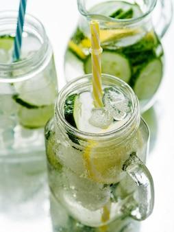 Bebida fresca de verano, agua con gas de desintoxicación saludable con limón y pepino en tarro de albañil, concepto de comida saludable,