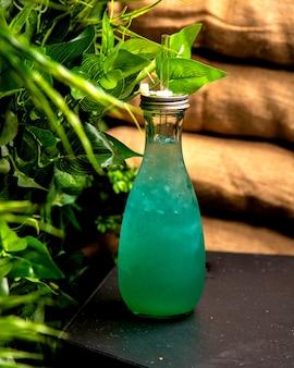 Bebida fría con hielo turquesa en una botella de vidrio.