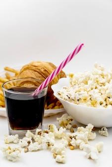 Bebida fría; paja; croissant con tazón de palomitas de maíz en mesa blanca