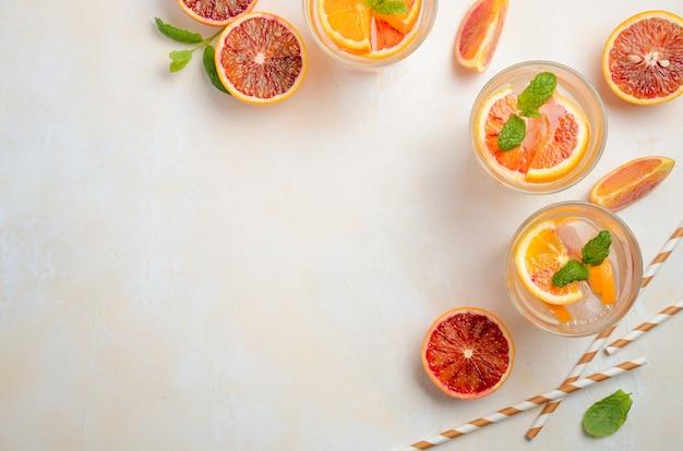 Bebida fría y refrescante con rodajas de naranja de sangre en un vaso sobre un fondo de hormigón blanco