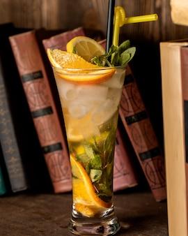 Bebida fría con rodajas de naranja y hojas de menta.
