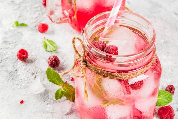 Bebida fría de verano, sangría de frambuesa, limonada o mojito con frambuesa fresca y jarabe, hojas de menta, en copyspace de piedra gris