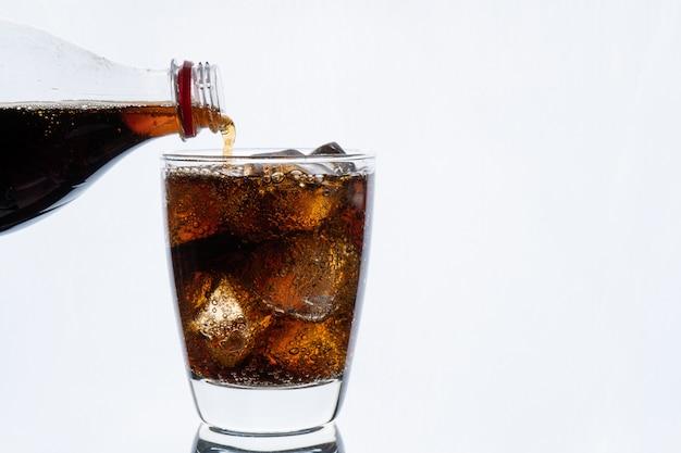 Bebida fría, vertiendo refrescos de botella, vaso de cola con hielo para bebidas calientes y de verano aislado en la pared blanca