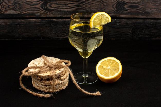 Bebida y galleta bebida de limón con trozos de limón dentro de vidrio transparente junto con galleta de pan redondo sobre una madera rústica