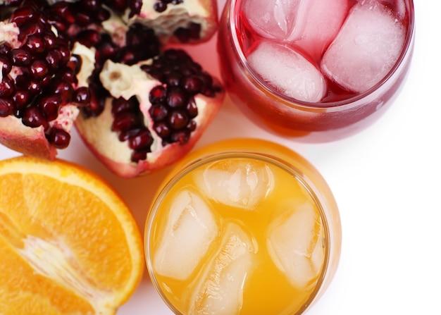 Bebida helada de granada y naranja con frutas frescas aisladas en blanco