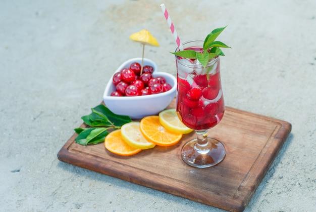 Bebida helada en un vaso con cerezas, limón, hojas de cerca sobre cemento y tabla de cortar