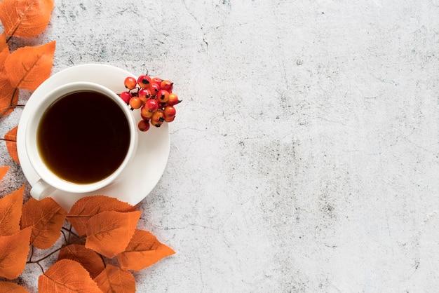 Bebida con hojas de otoño sobre superficie clara.