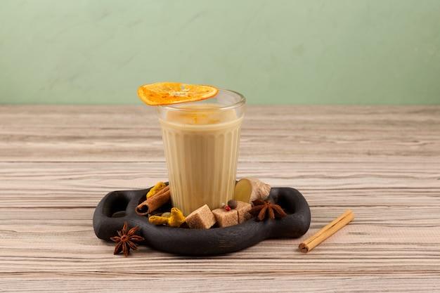 Bebida india popular té karak o masala chai. elaborado con la adición de leche, variedad de especias y especias. un vaso sobre una mesa de madera junto a los ingredientes, primer plano, copie el espacio.