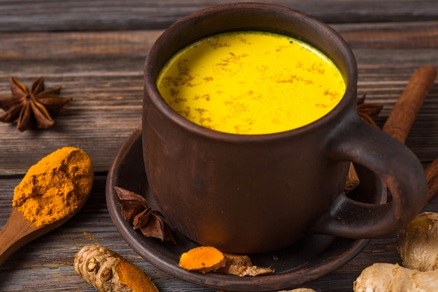 Bebida india tradicional cúrcuma con leche o leche dorada con canela, jengibre, anís, pimienta y cúrcuma