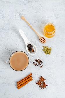 Bebida india tradicional té masala en una taza de vidrio con ingredientes para cocinar.