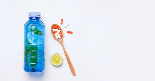 Bebida isotónica en botella junto a vitaminas y suplementos dietéticos