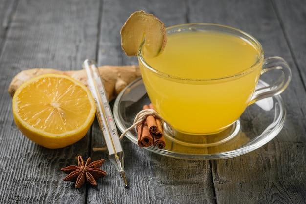 Bebida de jengibre para aumentar la inmunidad y un termómetro para medir la temperatura corporal en una mesa negra.
