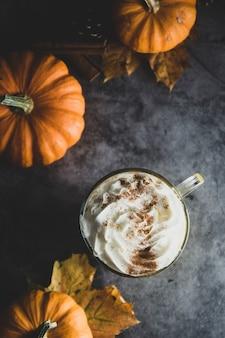 Bebida latte de calabaza de otoño con especias con canela y espuma de crema