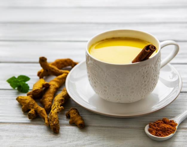 Bebida latte de cúrcuma amarilla. leche dorada con canela, cúrcuma, jengibre y miel sobre superficie de madera blanca.