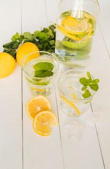 Bebida de limon en botella y vasos.