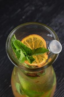 Bebida de limonada de agua de soda, limón y hojas de menta en frasco sobre fondo negro