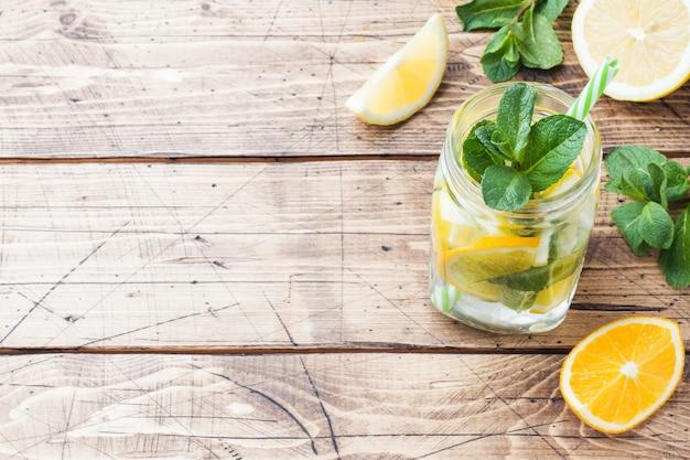 Bebida de la limonada del agua de soda, del limón y de las hojas de menta en tarro en fondo de madera. copia espacio