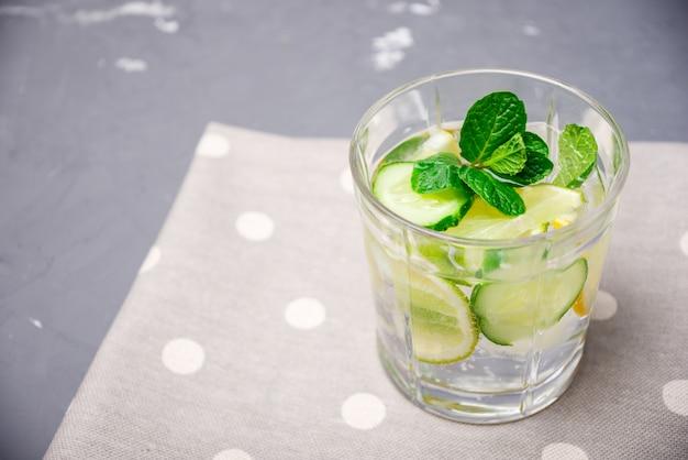 Bebida limpiadora de pepino, limón y menta sobre la mesa.