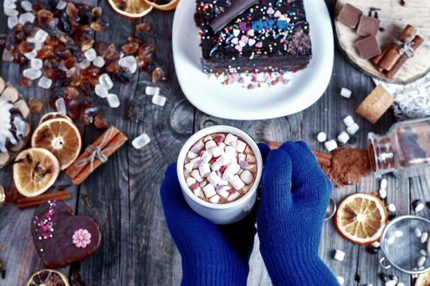 Bebida con malvaviscos en sus manos sobre una mesa con dulces