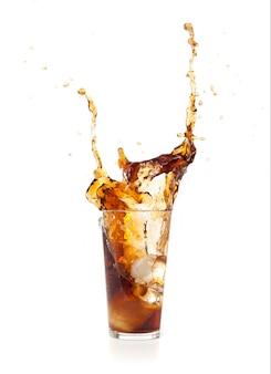 Bebida marrón cayendo un hielo dentro