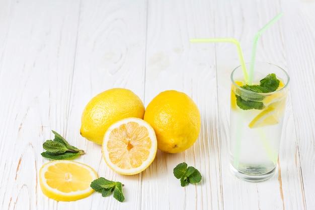 Bebida de menta cítrica fresca preparada y limones.