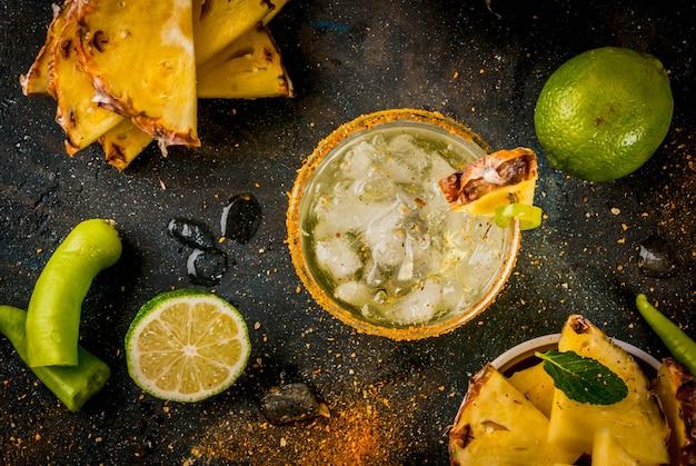 Bebida mexicana margarita picante cóctel con piña y jalapeño y lima fondo azul oscuro