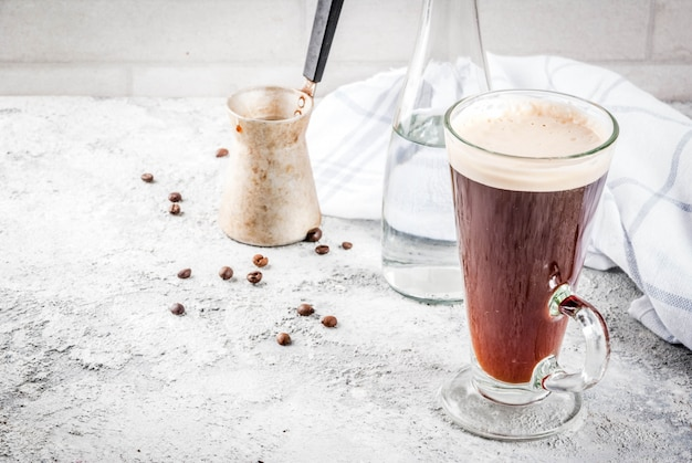 Bebida moderna y moderna. café expreso con agua mineral, con cafetera y granos tostados, superficie de piedra gris,