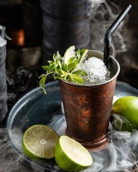 Bebida de mojito en vaso de acero con lima, menta y hielo