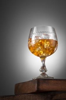 Bebida de naranja con hielo en vaso en la mesa de madera