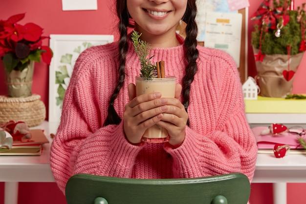 Bebida de navidad de invierno popular tradicional en manos de la mujer. mujer sonriente sin rostro con dos trenzas sostiene ponche de huevo relleno de canela y abeto, posa en la habitación cerca del escritorio