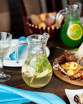 Bebida de pera con rodajas de pera y hojas de albahaca