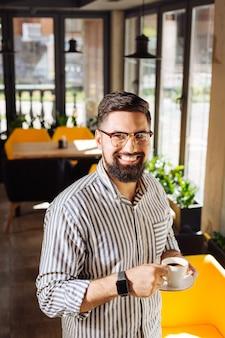 Bebida perfecta. buen hombre feliz sonriendo mientras disfruta de su espresso matutino