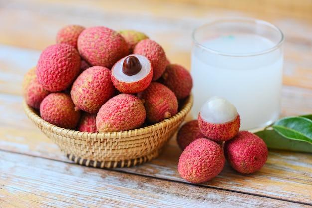 La bebida y la rebanada frescas del lichi peladas con las hojas verdes cosechan en cesta del verano de la fruta tropical del árbol en tailandia. jugo de lichi en mesa de madera