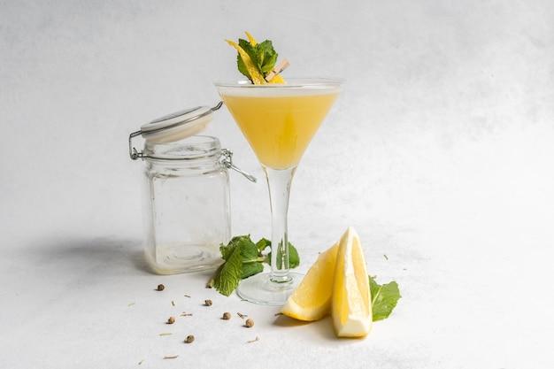 Bebida refrescante decorada con cáscara de limón y hojas de menta