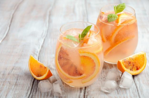 Bebida refrescante fría con rodajas de naranja sanguina en un vaso sobre una madera.