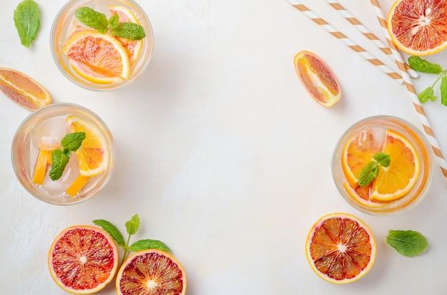 Bebida refrescante fría con rodajas de naranja sanguina en un vaso sobre una mesa de hormigón blanco