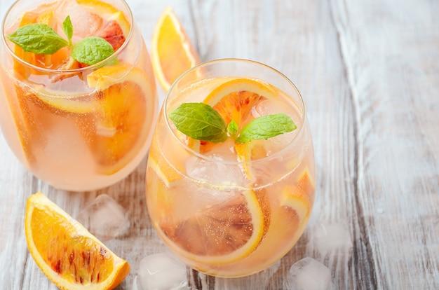 Bebida refrescante fría con rodajas de naranja sanguina en un vaso sobre una mesa de madera.