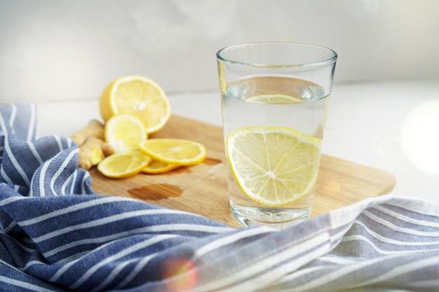 Bebida refrescante con limón. agua tibia con una rodaja de limón junto a una servilleta azul