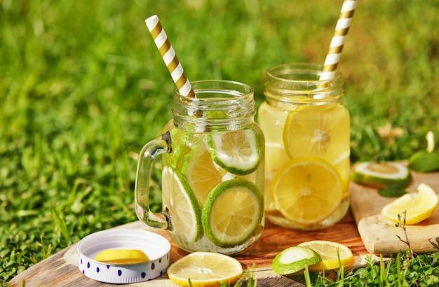 Bebida refrescante con limón y lima en frascos especiales con pajitas en un soporte de madera, rodada en la mañana sobre la hierba verde. concepto de alimentación saludable