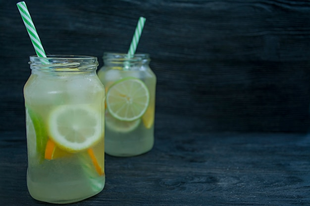 Bebida refrescante de verano de cítricos. beber de lima, limón, naranja. fondo de madera oscura