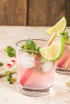 Bebida refrescante de verano cóctel mojito o limonada orgánica casera con ruibarbo, menta y lima en una mesa de piedra clara con vasos y una botella