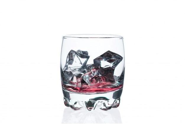 Bebida rosada con los cubitos de hielo en un vidrio en blanco. cóctel helado exótico.