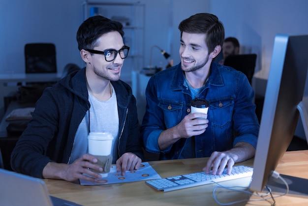 Bebida sabrosa. programadores positivos guapos riendo y disfrutando de su café mientras están sentados frente a la computadora