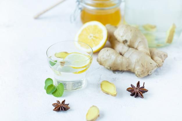 Bebida saludable de jengibre en una taza. raíz de jengibre, miel en un frasco, limón sobre una mesa blanca.