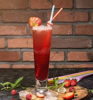 Bebida saludable refrescante de verano, batido de fresa o fresco con menta en un ladrillo de madera oscuro.