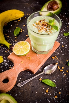 Bebida saludable de verano, batido de aguacate y plátano con lima, granola y leche de coco