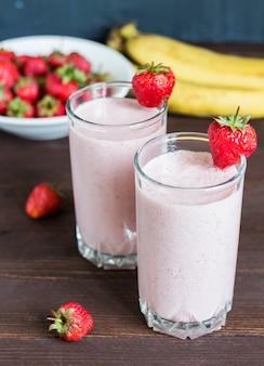 Bebida sana del desayuno del smoothie del plátano de la fresa en vidrio